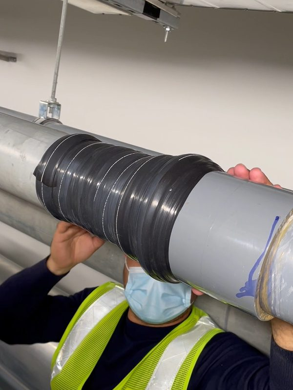 Wrap & Seal Pipe Burst Tape applied to a step joint on a 100mm UPVC pipe as part of a live leak repair